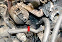 Use your two 13mm wrenches or sockets and remove the two nuts and bolts holding the trap to the lower mount (red arrow).