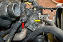 Remove the EGR tube using a 13mm wrench and remove the A/C bracket attached to the thermostat (yellow arrow).