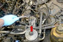 Disconnect the lines and remove the fuel filter and filter mounting bracket (red arrow).