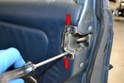 Use a Philips head screwdriver and remove the two Philips head screws and the latch surround from the panel (red arrows).