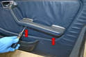 Next, remove the two large Philips head screws from the door arm rest (red arrows).