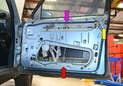 With the door panel and plastic vapor shield removed, you can see how the actuator located in the lower section of the door (red arrow) is connected to a rod (purple arrow) that runs to the door latch and lock (yellow arrow).