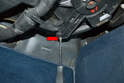 Next use a Philips head screwdriver and remove the single screw on the plastic arm on the blower motor (red arrow).