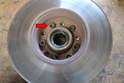 You are going to need to remove the five 10mm Allen bolts that attach the rotor to the hub (red arrow).