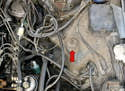 To replace the shocks begin by opening the hood and locating the top of the shock in the engine compartment (red arrow).