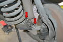 The lower shock is attached by two 10mm twelve point bolts (red arrows).