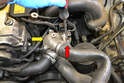 Working on the left side of the motor disconnect the upper radiator hose from the thermostat housing by removing the hose clamp (red arrow).