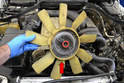 Wiggle the fan and clutch off the front of the pulley and remove it from the vehicle (red arrow).