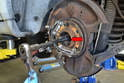 You do not need to remove the axle from the wheel hub before you start but I recommend you press the axle out or at least break its hold on the wheel hub before you loosen or remove everything.
