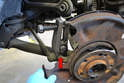 Separate the tie link from the knuckle using a ball joint or tie rod separator.
