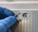 The plastic screws unscrew with a Philips head screwdriver then the base of the plug pulls out from the hole in the hatch.
