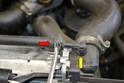 Use a flathead screwdriver and remove the clamp and then hose for the coolant overflow line (red arrow).