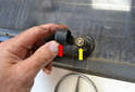 Working on the outside of the hatch flip up the cover on the wiper arm (red arrow) and remove the 13mm nut (yellow arrow) holding the wiper arm to the motor shaft.