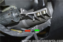 You will need to slide the steering column cover forward to cut the zip tie connection for the cruise control and turn signals located under the steering shaft (red arrow).