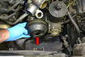 Remove the three 13mm bolts from the power steering pulley and remove the pulley (red arrow).