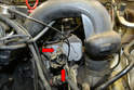 Remove the two 10mm nuts holding the throttle body section of the wiring to the engine mount (red arrows).