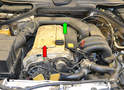 The six spark plugs on the M104 engine are located under a cover on the top of the valve cover (red arrow).