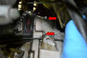 There are two 17mm bolts holding the starter motor to the bell housing (red arrows).
