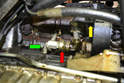 Working under the car, remove the 13mm nut holding the air pump tube and valve to the engine block (green arrow).