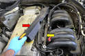 Lift the plastic cover off the wiring harness (red arrow) to expose the fuel rail below (yellow arrow).