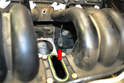 Separate the wiring connection for the knock sensor below the number four intake runner (red arrow).