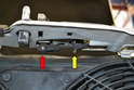 The cables grommet sits in a mount under the cross member (yellow arrow) and attaches to the mechanism (red arrow).