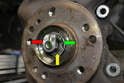 This photograph illustrates the washer (yellow arrow) that goes between the outer bearing (green arrow) and the axle nut (red arrow).