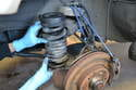 With the spring fully compressed, lower the control arm and remove the spring and rubber in a forward motion.