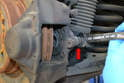 Use a 15mm wrench and loosen but do not remove the rubber brake line from the caliper (red arrow).