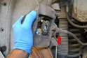 With the caliper off of the knuckle it is much easier to spin the caliper off of the brake hose (red arrow).