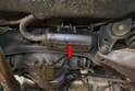 The rear pump draws gasoline directly from the tank and is located under a plastic cover mounted just behind the rear cross-member (red arrow).