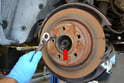 You are going to end up removing the brakes and rotor, but before you do you want to get the 30 mm 12 point nut (red arrow) off the axles.