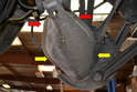 Remove the two 10mm bolts (red arrows) and the two clips (yellow arrows) and the plastic control arm protective cover.