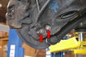 Remove the 17mm bolts attaching the shock to the control arm (red arrow) and slightly lift the control arm to slide the bolts out.