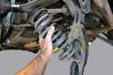While holding the spring and control arm, carefully swing the arm down from the wheel carrier and remove the spring.