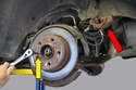 Remove the two 17mm bolts holding the caliper to the carrier and safely hang the caliper (red arrow), do not hang the caliper by the brake line! Using a 5mm Allen driver, remove the securing screw on the rotor.