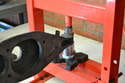 This photo illustrates how you can use a press to push out the old rubber bushing and install the new one.
