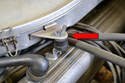 Remove the two wing nuts (red arrow, one on each side) attaching the air housing cover to the valve covers.