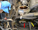 On the lower driver side of the pump use a 13mm wrench to loosen the front bolt (red arrow), and then working from the back turn the toothed bolt in its gear (yellow arrow).