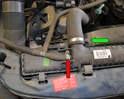 Undo and separate the overflow hose (red arrow) and upper hose (green arrow) from the radiator.