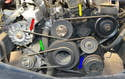 This photo illustrates the five different belts on the W126 (there are two belts on the water pump, power steering pump, yellow arrow).