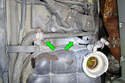 Remove the two 10mm mounting fasteners (green arrows) that hold down the back of the expansion tank to the inner fender of the car.