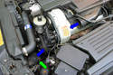 Pull the air intake tube off of its intake mount (green arrow) by pulling each end in the direction of the blue arrows.