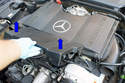 Remove the front engine cover by lifting it up off of the 4 spring clips that hold it in place by moving them in the direction of the blue arrow.