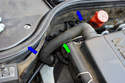 Working at the back of the right side engine cover/air filter housing remove the crankcase breather hose (green arrow) by moving each end in the direction of the blue arrow.