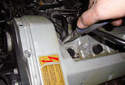 Remove the crankcase breather line from the valve cover by squeezing the clamp and pulling up on the hose.