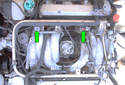 Remove the two 4mm Allen head fasteners (green arrows) that hold the plastic wiring harness cover to the fuel rail.