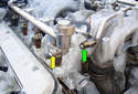 Remove the two feed and return fuel lines by threading off the 17mm flare fittings (green and yellow arrows) and remove from the rail.