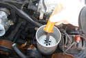 Remove the power steering fluid reservoir filter spacer.