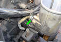 Pull the return hose out of the power steering fluid reservoir by moving back towards the engine.